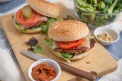Cheeseburgers with arugula salad on a table Stock Photos