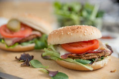 Cheeseburgers with arugula salad on a table Stock Photo