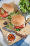 Cheeseburgers with arugula salad on a table Royalty Free Stock Images