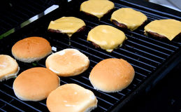Cheeseburgers cooking on the barbecue Stock Images
