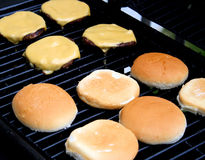 Cheeseburgers cooking on the barbecue Royalty Free Stock Images