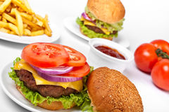 Cheeseburgers e fritadas imagens de stock