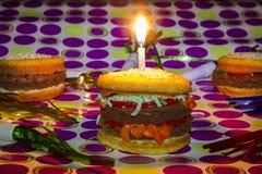 Cheeseburgers e hamburgrer do impostor da sobremesa com cand do aniversário Imagens de Stock