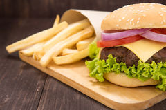 Cheeseburgers with french fries on wooden background Royalty Free Stock Photo