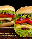 Cheeseburgers grandes en la estera de madera en fondo negro imagen de archivo libre de regalías