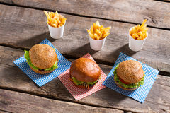 Cheeseburgers on napkins and fries. Stock Photo