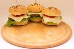 Cheeseburgers sabrosos en un tablero de madera Fotografía de archivo