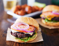 Cheeseburgers with wings and beer. Shot on wooden table Stock Photo