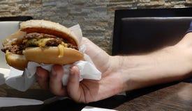Cheeseburgher cozinhado mostrado em uma mão fotos de stock
