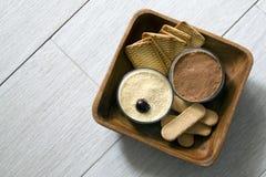 Cheesecake γάλακτος, που διακοσμείται με τα κεράσια, στα γυαλιά με τα μπισκότα σε ένα ξύλινο κύπελλο σε μια πορσελάνη το πρωί αρχ Στοκ Εικόνες