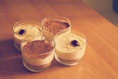 Cheesecake γάλακτος στα γυαλιά, που διακοσμούνται με crumbs καφέ, μπισκότα και κεράσια, σε έναν ξύλινο πίνακα σε ένα θολωμένο υπό Στοκ Εικόνες