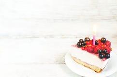 Cheesecake γενεθλίων με το κερί, τα σμέουρα, το κόκκινο και μαύρο curr Στοκ Εικόνες