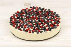Cheesecake με τις κόκκινες σταφίδες και τα βακκίνια στο ξύλινο υπόβαθρο Στοκ φωτογραφία με δικαίωμα ελεύθερης χρήσης