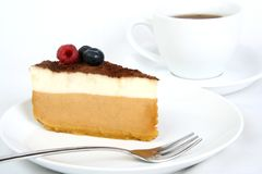Cheesecake. On white plate with tea in background Stock Photos
