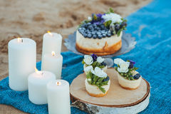 Free Cheesecake And Capcakes Decorated By Blueberries And Flowers On The Sand. Concept Date,proposal, Picnic. Natural Food Royalty Free Stock Photo - 93323545
