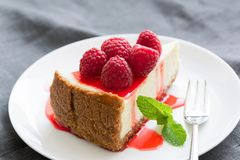 Cheesecake with berry sauce and fresh raspberries on white plate. Selective focus, horizontal composition Royalty Free Stock Images