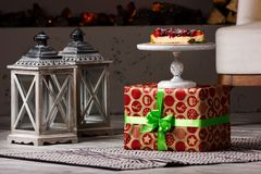 Cheesecake with berry in still life. Delicious cheesecake section with different berry on the present box with gray lanterns on the floor Stock Images