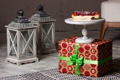 Cheesecake with berry in still life. Delicious cheesecake section with different berry on the present box with gray lanterns on the floor Stock Photos