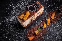 Cheesecake on a black background with dried fruit and mint sprinkled with powder stock images