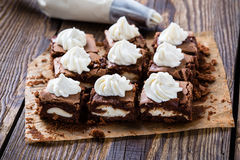 Cheesecake brownies with cream cheese swirled frosting. And pastry tip in background royalty free stock photo