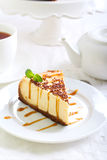 Cheesecake with caramel drizzle. Served on plate Stock Images