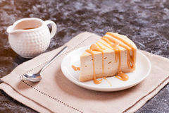 Cheesecake with caramel drizzle, served on plate. Close up, horizontal stock photo