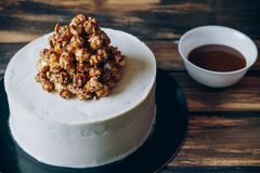 Cheesecake with caramel popcorn and chocolate souse on the wooden background top view. Artwork. Stock Image