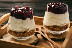 Cheesecake with cherry jelly in glass jars. Royalty Free Stock Images