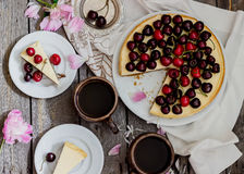Cheesecake with cherry, two slices on saucers and metal tray  on a wooden table. . Stock Image