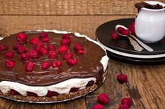 Cheesecake with chocolate and raspberries. Unbaked cheesecake with chocolate and raspberries on a wooden table Royalty Free Stock Photos