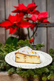 Cheesecake in christmas eve setting. Poinsettia flower in the ba Stock Image