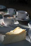 Cheesecake and coffee. Slice of baked cheesecake with cups of coffee in the background. Shallow depth of field Stock Photography