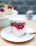 Cheesecake, cream mousse cake with fresh berries on a white plate Selective focus. Cheesecake, cream mousse cake with fresh berries on a white plate Grey stone Stock Photos