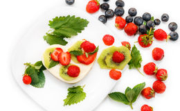 Cheesecake decorated with fresh berries. Heart-shaped cheesecake decorated with fresh strawberries and kiwi, isolated on white Stock Photography