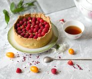 Cheesecake decorated with raspberries on a saucer. Cup of black tea. stock image