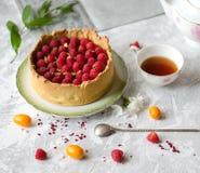 Cheesecake dekorujący z malinkami na spodeczku czarną herbatę obraz stock