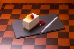Cheesecake dessert. Decorated with raspberry on wooden table Royalty Free Stock Image