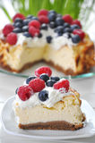 Cheesecake with fresh berries. On a table with flowers in the background Stock Photos