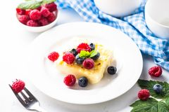 Fresh raspberries in wooden bowl on white table. Cheesecake with fresh berries on white plate. Healthy breakfast Stock Photography