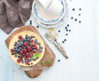 Cheesecake with fresh raspberries and blueberries. Homemade cheesecake with fresh raspberries and blueberries on a wooden serving board, plates, cups, kitchen Royalty Free Stock Photos