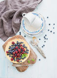 Cheesecake with fresh raspberries and blueberries. Homemade cheesecake with fresh raspberries and blueberries on a wooden serving board, plates, cups, kitchen Stock Photography