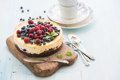 Cheesecake with fresh raspberries and blueberries. Homemade cheesecake with fresh raspberries and blueberries on a wooden serving board, plates, cups, kitchen Stock Images