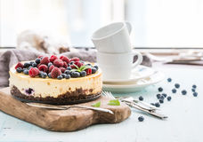 Cheesecake with fresh raspberries and blueberries. On a wooden serving board, plates, cups, kitchen napkin, silverware over blue background, window at the Stock Photography