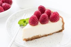 Cheesecake with fresh raspberries on white plate. Closeup view, selective focus Stock Images