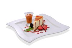 Cheesecake with fresh strawberries and blackberry. On a white plate. Isolated stock image