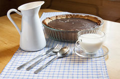Cheesecake in a glass baking dish and milk jug Stock Image