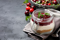 Cheesecake in a glass jar with cherries Royalty Free Stock Image