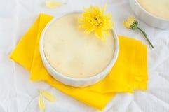 Cheesecake i kwiat na żółtej pielusze i białym tablecloth Obraz Stock