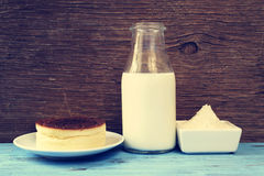 Cheesecake and the ingredients to prepare it, with a filter effe. A cheesecake and some of the ingredients to prepare it, such as light cream or wheat flour, on Royalty Free Stock Photos