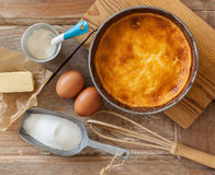 Cheesecake with ingredients. A warm cheesecake just from the oven with kitchen utensils and ingredients on a wooden table Royalty Free Stock Photo